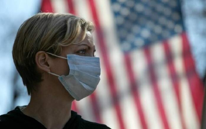 A woman wearing a mask with the US flag in the background. (File Photo, Image credit: USNews.com)