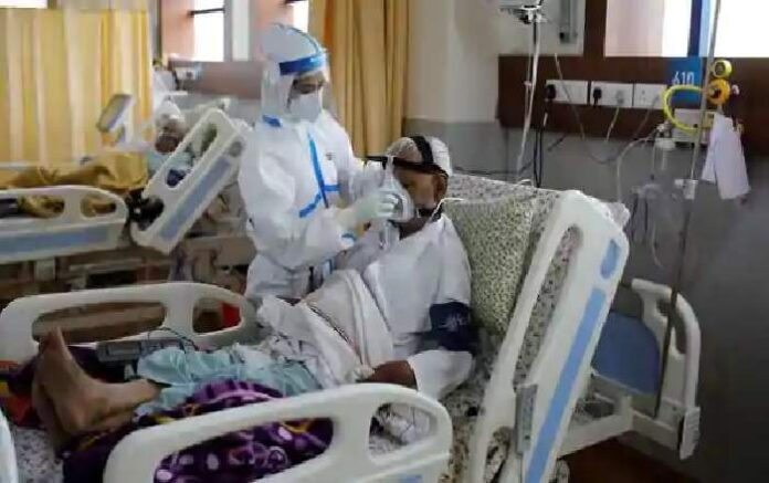 A medical worker takes care of a patient suffering from COVID-19 at a hospital in Noida (Image credit: Mint)