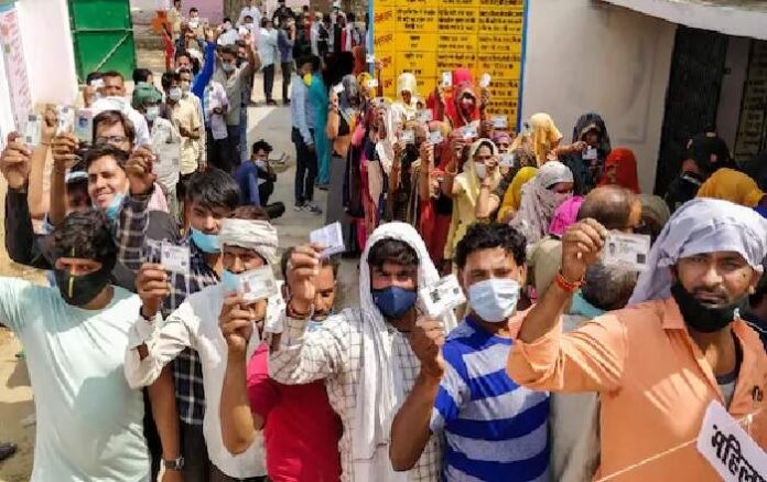 People show their voter ID as they stand in queue to cast their vote for Uttar Pradesh Panchayat election in Agra (Image credit: News18)