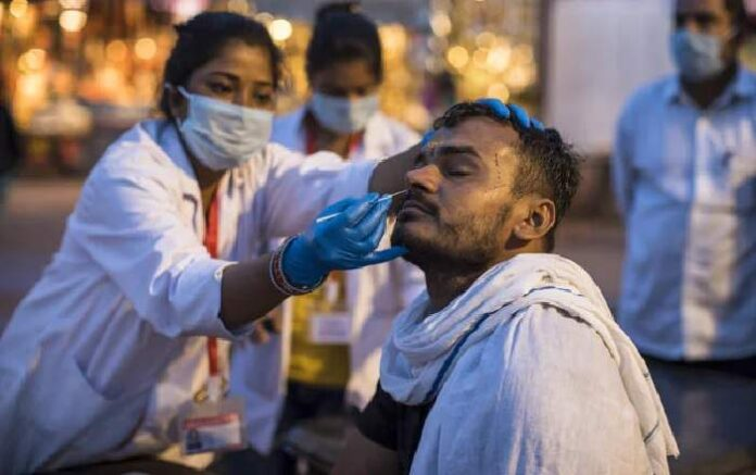 A health worker collects a sample using a swab from a person at a health centre (Image credit: NDTV)